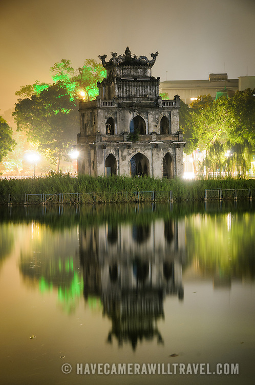 Turtle Tower (Thap Rua) is reflected on the still waters of Hoan Kiem Lake on a foggy Hanoi night.