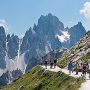 """The peaks of the Cadini Group jut high in the Dolomites near Cortina d'Ampezzo, Italy, Europe. In the Cadini di Misurina, Cima Grande rises to 2999 meters (9839 feet), between Cima Piccola 2857 m (9373 ft) and Cima Ovest or """"Western Peak"""" 2973 m (9754 ft). Hike for spectacular views around Tre Cime di Lavaredo (Italian for """"Three Peaks of Lavaredo,"""" or in German called Drei Zinnen, """"Three Merlons""""). The Dolomites are part of the Southern Limestone Alps, in northern Italy, Europe. UNESCO honored the Dolomites as a natural World Heritage Site in 2009."""