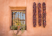Chili pepper ristras and iron-grated window; Old Town Albuquerque, New Mexico.