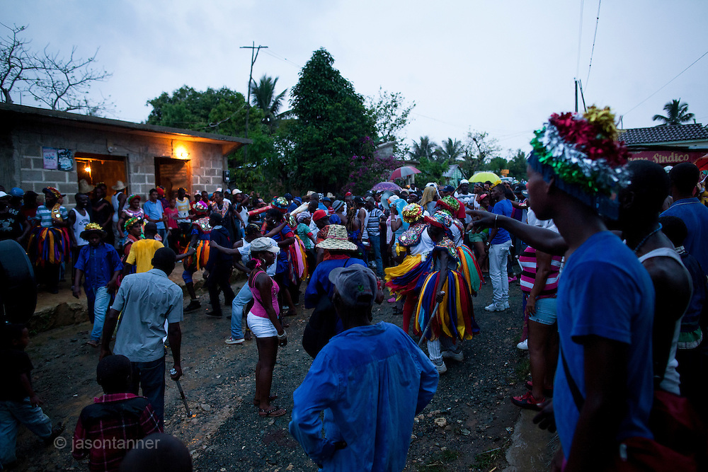 Dominican Republic: Residents of the former Batey, Haina look on at dusk as  Musicians, Dancers, Mayores and wait for a blessing from a local priest and perform as part of the GaGá  procession of El GaGá de San Luis....