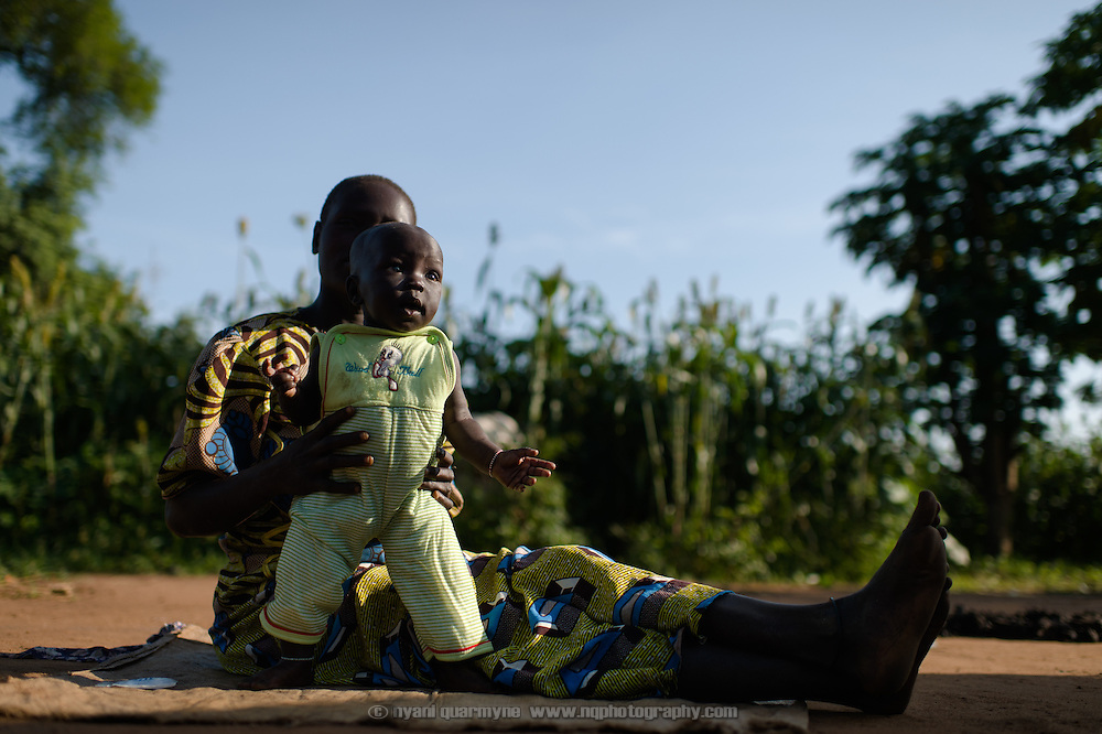 Regina Iyom and her son, James Okwang Okello, in front of their home in Imurok Payam in Eastern Equatoria, South Sudan on 9 August 2014. Regina's husband is a government soldier, and has been away for about a year. Having come to her current home after having had to flee fighting in Juba in December 2013, she says she receives no support from him—locals say that soldiers frequently go unpaid for long periods of time. Facing acute food insecurity, Regina received seed to plant from Plan International. (On the day she was pictured, she was very unwell, indicating that she had malaria.)