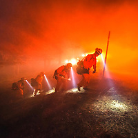 An inmate hand crew from Norco walks back to Table Mountain Rd after digging hand-line at the Pine Fire early Saturday morning. <br /> <br /> <br /> The North fire burns near Hesperia in San Bernardino County early Saturday morning July 18, 2015. The fire burned approximately 3,500 acres and was 35% contained. Nearby in Wrightwood the Pine Fire burned over 125 acres and was 0% contained. Evacuations were in place for both fires.