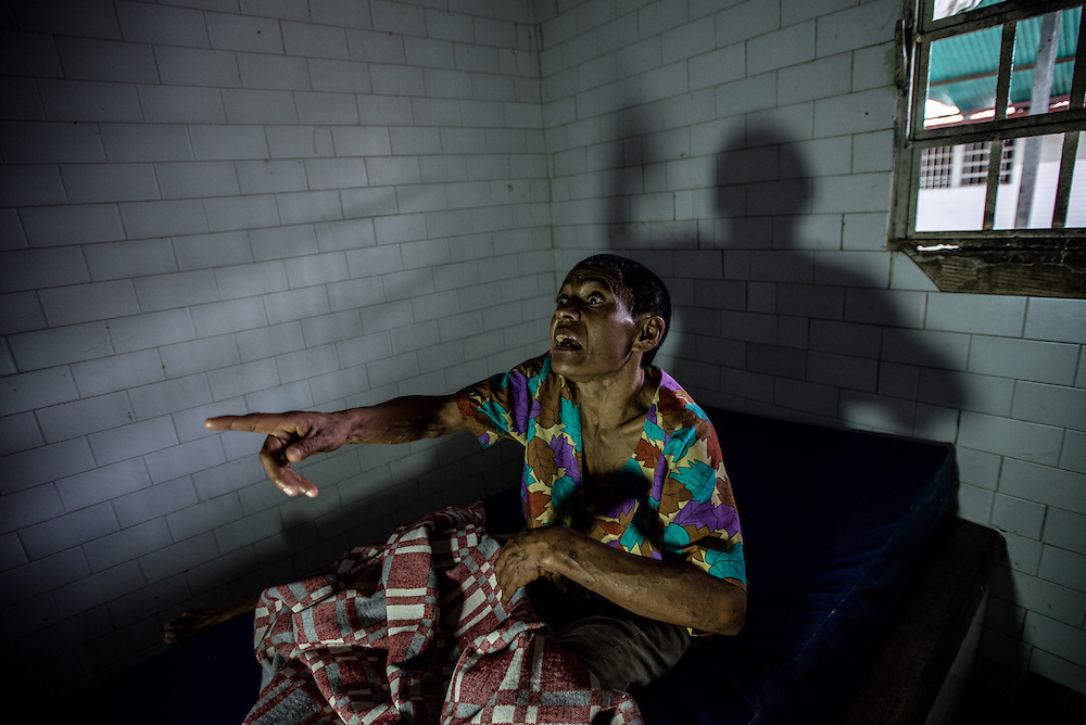 BARQUISIMETO, VENEZUELA - AUGUST 24, 2016: Margarita Silva, a paranoid schizophrenic, yells at nurses from her solitary confinement cell, where she was being held because two days earlier she attacked another patient in the middle of the night, and bit off her nose and ate it. The nursing staff said she had been without two of the medicines she needs to take to control her disorder when the attack occurred, and that they believe that it is unlikely that she would have acted out if she had been medicated, or if she had been under the regular care of a psychiatrist. The economic crisis that has left Venezuela with little hard currency has also severely affected its public health system, crippling hospitals like El Pampero Psychiatric Hospital by leaving it without the resources it needs to take care of patients living there, the majority of whom have been abandoned by their families and rely completely on the state to meet their basic needs. The hospital has not employed a psychiatrist for over two years. Drugs used to combat bipolar disorder, epilepsy, schizoaffective disorder and chronic anxiety are now in short supply, as are numerous sedatives and tranquilizers needed to care for patients. Members of the nursing staff debate daily which patients are the most unstable, to decide which patients will receive pills and which will go without. When a patient loses control, often the only thing they can do is restrain them, or lock them in an isolation cell to prevent them from hurting themselves, other patients and members of the staff.  PHOTO: Meridith Kohut