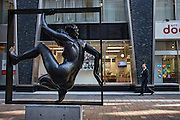 Salaryman passing in front of a street sculpture in Marunouchi area of Tokyo