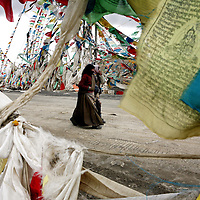 Two women walk by a remote mountain pass covered in Tibetan prayer flags in route to Mt. Everest, part of the Himalayan mountain range, in Tibet, in western China. (Photo/Scott Dalton)