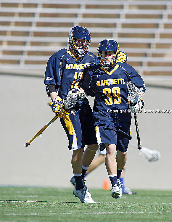 SHOT 3/2/13 1:00:15 PM - Marquette's Conor Gately #12 celebrates a goal by teammate Henry Nelson #39 against Air Force during their college lacrosse game at Falcon Stadium in Colorado Springs, Co. Marquette won the game 8-6 marking their first ever win as a new program. (Photo by Marc Piscotty / © 2013)