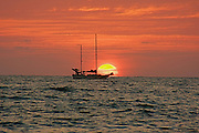 A sailboat sails into the sunset at the Bay of Banderas Mexico.