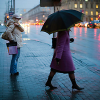 Under a light rain, pedestrians wait to cross the main road through downtown Minsk on Oct. 22, 2009.