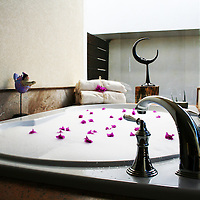 Romantic bath tub filled with bubbles and covered with bugambilia flower petals. Photograph is taken in El Rincon Villa in Pedregal residential community, in Cabo San Lucas.