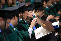 05/17/2015 - Medford/Somerville, MA - A newly minted doctor looks over his degree at Tufts University School of Medicine and Sackler School of Graduate Biomedical Sciences's Phase II ceremony in Gantcher Center during Tufts University's 159th Commencement on Sunday, May 17, 2015.(Matthew Healey/Tufts University)
