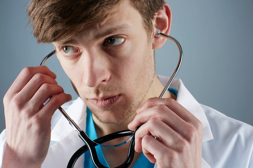 A portrait series representing the intense emotions that Doctors face.  A white male Doctor wearing a white lab coat, stethoscope, and blue medical scrub suit shown.