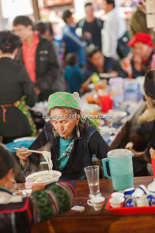 A hilltribe woman with her distictive outfit eats a noodle soup in the markets  of Sapa, Vietnam.