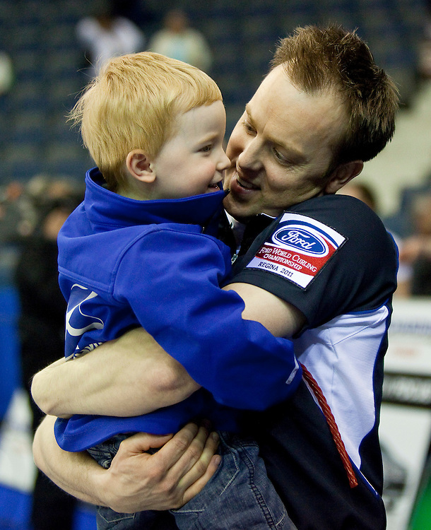 Scottish skip Tom Brewster celebrates with his son ethan Scotland's 7-6 win in their semi-final against Norway at the Ford World Men's Curling Championships in Regina, Saskatchewan, April 9, 2011. The Scottish team will face Canada in the final Sunday.<br /> AFP PHOTO/Geoff Robins
