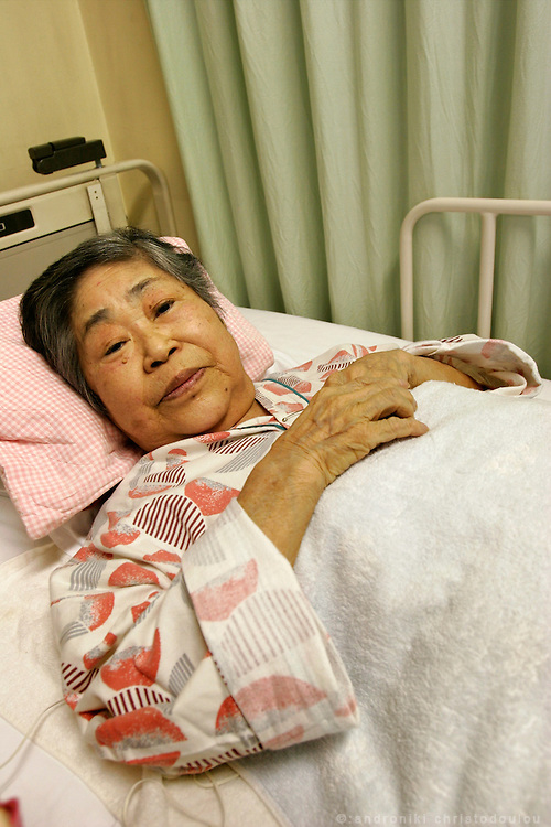 "SUZUKO NUMATA: Pictured in hospital, where she is being treated for osteoporosis.  Numata was 20 and engaged to be married when the bomb fell and shattered her left leg.  Three days later it began to fester and was amputated below the knee, without anesthetic. She later learned that her fiancé had been killed.  She never married and spent her life teaching and unable to talk about what happened until she retired twenty years ago.  ""We used to chant during the war: Be united in one mind like a fireball, 100 million people. Then when the bomb fell the trucks came around and ignored women and children, and just helped the healthy men.  That's when I first understood what war was."""