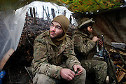 Cowboy (le.) sits beside Charlie who cleans his Kalashnikov in the frontline trench.<br /> <br /> Fascinated by war and convinced of a simple shaped nationalistic ideology, five vonuteer warriors from Europe and USA left behind their former lifes. Walking into battle in Ukraine, Ben, Alex, Craig, Charlie and Cowboy made it to the frontline and joint the right-wing militia Right Sector, supporting the ukrainian army which is short of staff. Receiving no payments but shelter, food and ammo the foreigners selfmade battlegroup Task Force Pluto is a loose union of individuals and no particular ukrainian phenomenon. The Boom Stick Brotherhood would move on to another conflict around the globe when Ukraine become boring to them. They want to be involved in battle. That&acute;s what they are aiming for. Living a dream of smoking guns, camaraderie and outdoor life. An extreme lifestyle devoted to an everyday look into the face of death.<br /> <br /> The Boom Stick Brotherhood is a multi-national, multi-religious and multi-ethnic group:<br /> Ben, an austrian infantryman travelling hot zones since years. Bored by his own reluctant national army at home he made plenty of experience in Kosovo, Syria, Iraq and Ukraine.<br /> Alex, Ben&acute;s brother in arms from austrian army times deserted and fled the country to get ultimately involed in frontline fights.<br /> Craig was fighting almost 6 years for the US-Army in Iraq and Afghanistan but got in conflict with the law afterwards. He escaped conviction by going abroad.<br /> Charlie was totally bored by his californian routine in Silicon Valley but failed to join the US-Army and French Foreign Legion. Eventually he found battle opportunities in Ukraine.<br /> Petty crook Cowboy got in trouble with US law only days before his Army unit was to deployed to Afghanistan. Later during a day release he made it from prison to France but French Foreign Legion rejected him. He gave Ukraine a go.