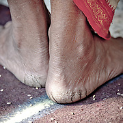 Detail of feet from Indian priest wearing a traditional lungi in white and red.