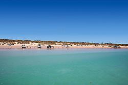 Tourists enjoy the sunshine on Broome's Cable Beach near high tide.