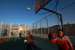 Migrant children play in a basketball court beside a newly opened community centre built out of shipping containers by non-profit organisation Compassion for Migrant Children (CMC) in a migrant community in Beijing, China on 24 March 2011. CMC started the mobile community centre for migrant children and their families from containers custom made to fit as classrooms, computer labs, and offices. This is the first time the non-profit organisation is setting up a new container community centre to cater to the growing needs of migrant workers in the city who are often forced to move when the area they live in are redeveloped or demolished. The community centre will offer vocational training for youths, extracurricular activities for children, training for new mothers and family health