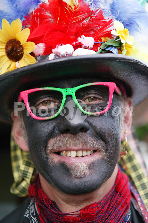 Portrait of Morris dancer wearing costume and makeup smiling,