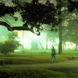 BUENOS AIRES, ARGENTINA: A man walks through a park in Buenos Aires, Argentina after dusk.  (Photo by Ami Vitale)