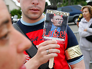 A Michael Jackson fan displays a picture depicting Santa Barbara county district attorney Tom Sneddon as the devil outside the courthouse where the Jackson trial is taking place in Santa Maria, California June 3, 2005. The closing arguments in the Jackson sexual abuse case were expected to conclude today.