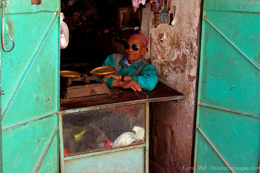 Africa, Morocco, Ouarzazate. Shop vendor relaxing in shade.