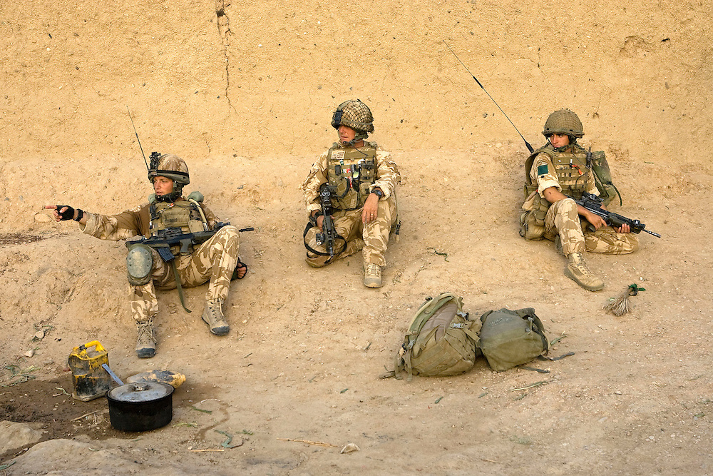 British soldiers of 3rd Battalion The Parachute Regiment take a break whist searching for insurgents after a dawn assault on a compound as part of Operation 'Southern Beast'. Kandahar Province, Afghanistan on the 6th of August 2008.