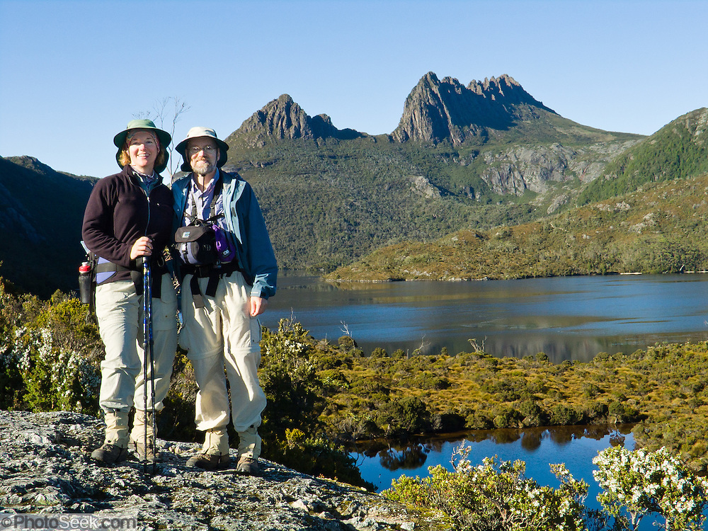 Bushwalkers enjoy Cradle Mountain (1545 m or 5069 ft)and Dove Lake, in Cradle Mountain - Lake Saint Clair National Park, Tasmania, Australia. The Tasmanian Wilderness was honored as a UNESCO World Heritage Site in 1982, expanded in 1989. The most extensive dolerite formations in the world dominate the landscape of Tasmania, where magma intruded into a thin veneer of Permian and Triassic rocks over perhaps a million years during the Jurassic breakup of supercontinent Gondwana in the Southern Hemisphere, forming vast dolerite/diabase sills and dike swarms. (North American geologists use the term diabase instead of dolerite to refer to the fresh, unaltered rock.) For licensing options, please inquire.