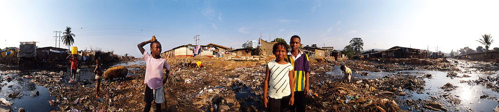 Bilal, Madeleine and Chris (left to right) on the Crocodile River while other children scavenge from the garbage, Kroo Bay, Freetown, Sierra Leone.