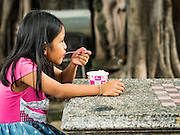 27 AUGUST 2016 - BANGKOK, THAILAND: A girl who lives in the Pom Mahakan slum eats a Thai crushed ice dessert during a lunch in the Pom Mahakan slum. The Pom Mahakan community is known for fireworks, fighting cocks and bird cages. Mahakan Fort was built in 1783 during the reign of Siamese King Rama I. It was one of 14 fortresses designed to protect Bangkok from foreign invaders. Only two of the forts are still standing, the others have been torn down. A community developed in the fort when people started building houses and moving into it during the reign of King Rama V (1868-1910). The land was expropriated by Bangkok city government in 1992, but the people living in the fort refused to move. In 2004 courts ruled against the residents and said the city could evict them. The city vowed to start the evictions on Sept 3, 2016, but this week Thai Prime Minister Gen. Prayuth Chan-O-Cha, sided with the residents of the fort and said they should be allowed to stay. Residents are hopeful that the city will accede to the wishes of the Prime Minister and let them stay.       PHOTO BY JACK KURTZ