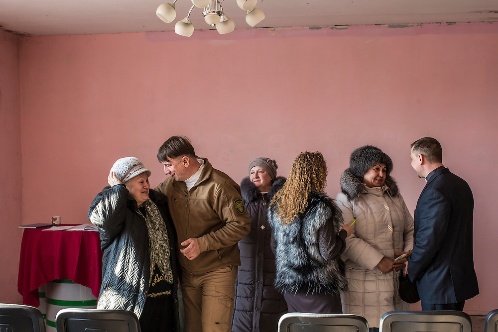 MARIINKA, UKRAINE - FEBRUARY 20, 2016:  Pastor Sergei Kosyak, right, talks with congregants after a service at the Christian Help Center of the Church of the Transfiguration in Mariinka, Ukraine. The Donetsk suburb has been the scene of some of the heaviest fighting recently between Ukrainian forces and pro-Russian rebels. CREDIT: Brendan Hoffman for The New York Times