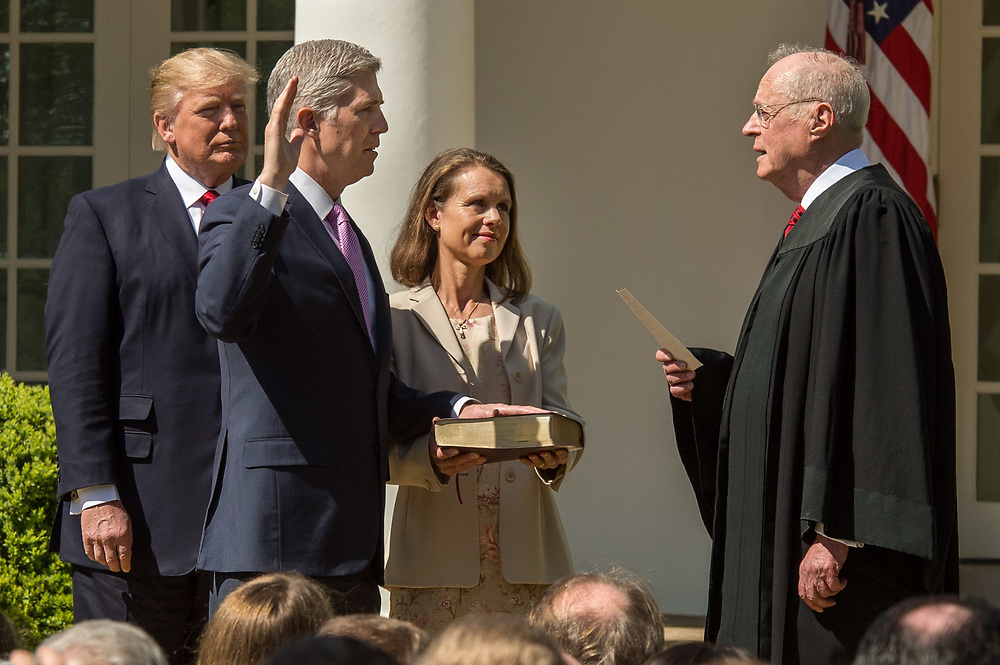 The Honorable Neil Gorsuch, second left, is sworn in by Supreme Court Justice Anthony Kennedy, right, while and U.S. President Donald J. Trump Gorsuch's wife Louise look on in the Rose Garden of the White House. Gorsuch replaces the seat vacated by Antonin Scalia when he died.