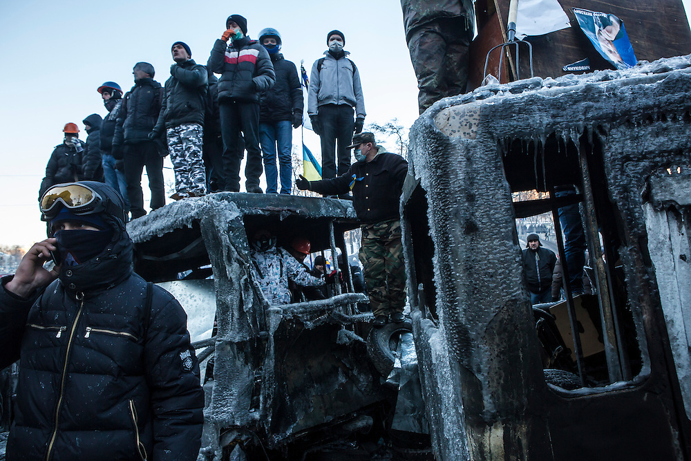 KIEV, UKRAINE - JANUARY 24: Anti-government protesters stand atop the burned out wreckage of buses, now covered in ice from fire hoses, on a street near Dynamo stadium on January 24, 2014 in Kiev, Ukraine. After two months of primarily peaceful anti-government protests in the city center, new laws meant to end the protest movement have sparked violent clashes in recent days. (Photo by Brendan Hoffman/Getty Images) *** Local Caption ***
