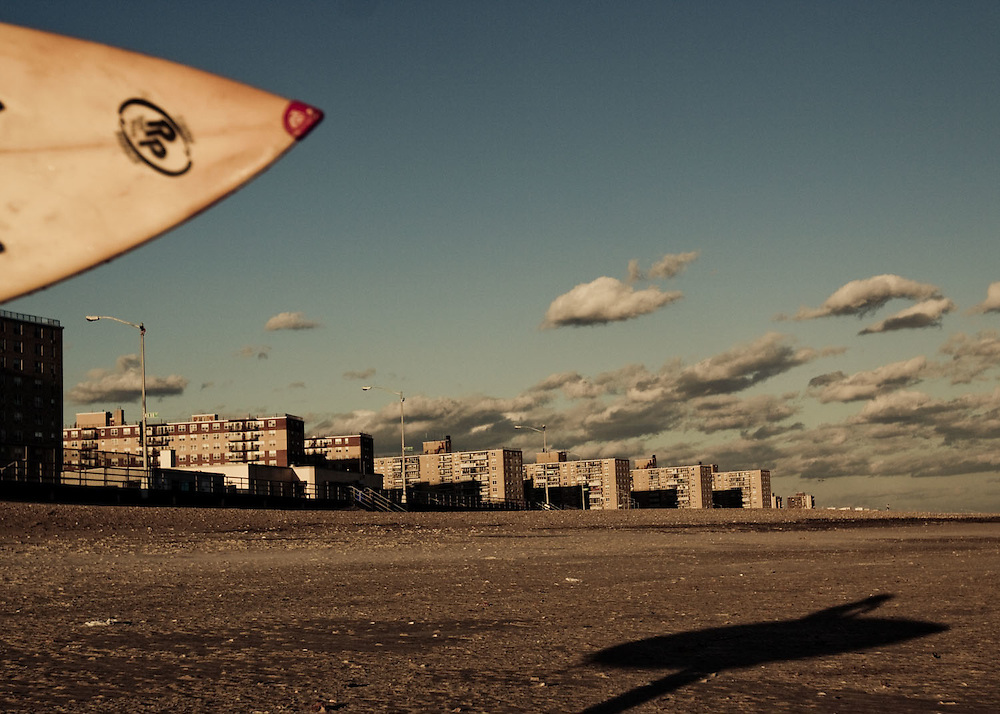 A surfer watches the surf from Beach 91, Rockaway Beach, Queens, NY.