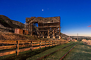 Venus, very bright as an evening star, shines over the old historic Atlas Coal Mine in the Red Deer River Valley, Alberta, near East Coulee. The mine buildings are the last standing from many coal mines that operated in the valley up until the 1970s. The Atlas Coal Mine is now a museum and National Historic Site.<br /> <br /> Mercury shines at right just above the horizon. The nearly Full Moon provides much of the illumination, though a sodium vapour light also provides some of the warm light to the foreground.