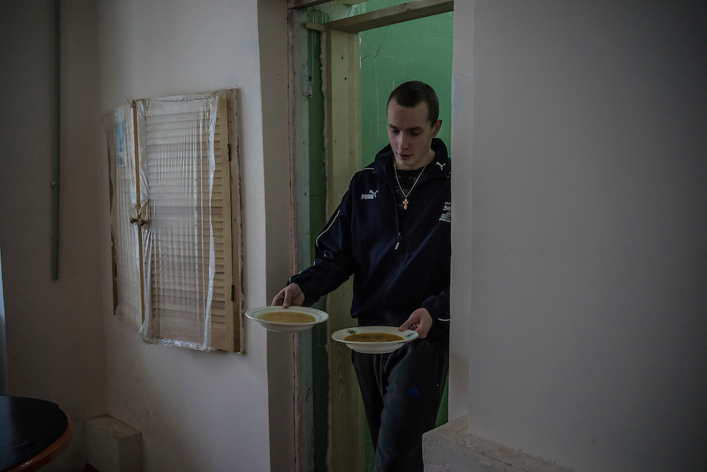 A security guard carries bowls of soup at Romashka, a summer camp where he and several hundred other people live after being displaced by fighting in Eastern Ukraine on Friday, February 13, 2015 in Kharkiv, Ukraine.