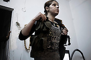 """SYRIA, ALEPPO : A Kurdish woman fighter of the """"Popular Protection Units"""" (YPG) stands between two comrade fighters inside a building in the majority-Kurdish Sheikh Maqsud district of the northern Syrian city of Aleppo, on April 16, 2013. ALESSIO ROMENZI"""