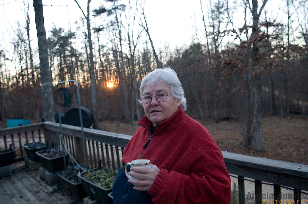 """Winnie Adams, 66, stands on the porch of her home at Alapine, a """"womyn's land"""" or lesbian intentional community, in rural northeast Alabama. ..(*the exact town/location of the community cannot be revealed in the caption or article, per agreement with the subjects)..Photo by Angela Jimenez for The New York Times .photographer contact 917-586-0916"""