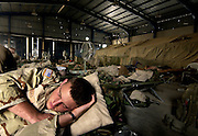 After standing guard during the night, a soldier tries to sleep at an abandoned car dealership in Baghdad, Iraq, on Oct. 18, 2003.