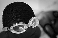 A student adjusts his goggles at a swim class that Jane Katz, a professor at at the John Jay College leads  for incarcerated youths at the school's pool in New York, July 17, 2010. Keith Bedford for the New York Times