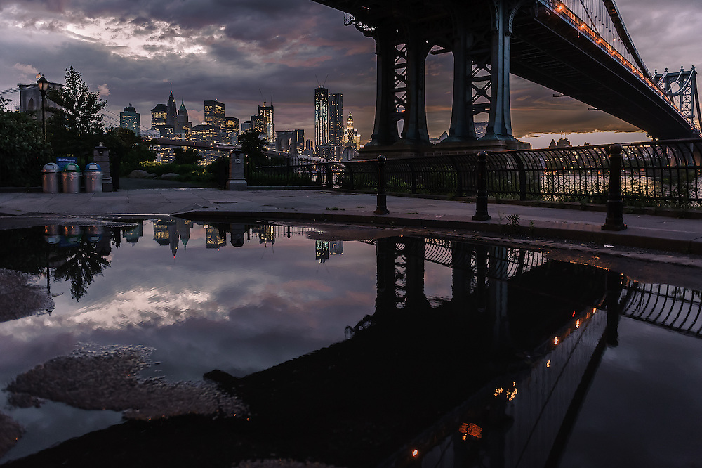 Reflection of the Manhattan Bridge pillar in a puddle with Manhattan and the Brooklyn bridge in the background, DUMBO, Brooklyn