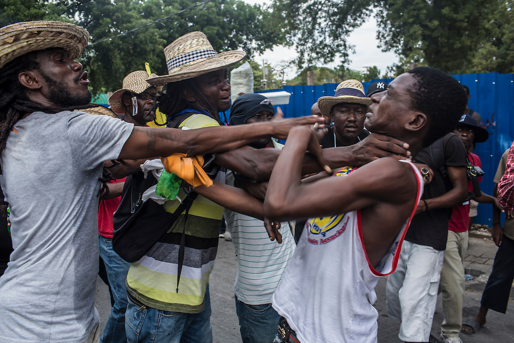 Anti-government protesters confront a pro-government man accused of stealing a cell phone on Tuesday, December 16, 2014 in Port-au-Prince, Haiti. President Michel Martelly was elected in 2010 with great hope for reforms, but in the wake of slow recovery and parliamentary elections that are three years overdue, his popularity has suffered tremendously, forcing Prime Minister Laurent Lamothe to resign.