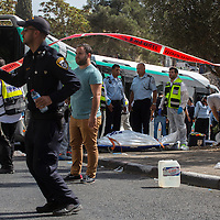 Israeli ZAKA emergency response members stand next to a body of an Israeli victim at the scene of a shooting attack in Jerusalem, Tuesday, Oct. 13, 2015. A pair of Palestinian men boarded a bus in Jerusalem and began shooting and stabbing passengers, while another assailant rammed a car into a bus station before stabbing bystanders, in near-simultaneous attacks that escalated a month long wave of violence. Two Israelis and one attacker were killed.<br /> Photo by Olivier Fitoussi.