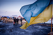 "The Ukrainian flag at the barricades blockading a building supplies store named ""Epicenter"" in the city of Lviv, Ukraine. In the back visitors and activists."