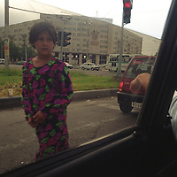 A young Uzbek girls asks for money from cars stopped at traffic lights in Tashkent, one of the Central Asian cities on the old SIlk Road trading route. Uzbekistan.