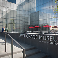 Vistors sit and enjoy the summer weather at the Anchorage Museum Rasmuson Center