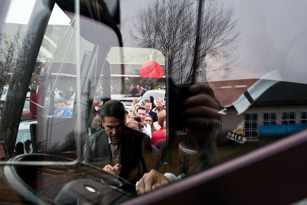 Republican presidential candidate Rick Perry boards his campaign bus after speaking at the Fainting Goat on Friday, December 30, 2011 in Waverly, IA.