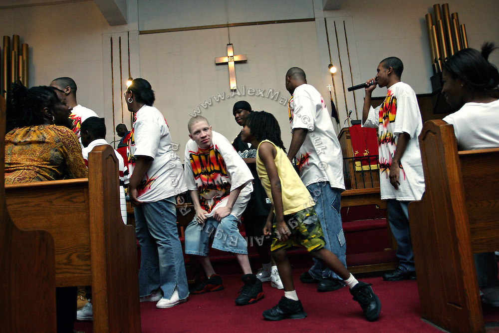 The Hells Most Wanted, a Christian Hip Hop group, and other members of the Hip Hop Church Choir, are singing and dancing in front of the altar during a Mass Service at the Hip Hop Church in Harlem, New York, NY., on Thursday, June 29, 2006. A new growing phenomenon in the United States, and in particular in its most multiethnic city, New York, the Hip Hop Church is the meeting point between Hip Hop and Christianity, a place where ?God? is worshipped not according to religious dogmatisms and rules, but where the ?Holy Spirit? is celebrated by the community through young, unique, passionate Hip Hop lyrics. Its mission is to present the Christian Gospel in a setting that appeals to both, those individuals who are confessed Christians, as well as those who are not regularly attending traditional Services, while helping many youngsters from underprivileged neighbourhoods to feel part of a community, to make them feel loved and to help them not to give up when problems arise. The Hip Hop Church is not only forward-thinking but it also has an important impact where life at times can be difficult and deceiving, and where young people can be easily influenced for the worst purposes. At the Hip Hop Church, members are encouraged to sing, dance and express themselves in any way that the ?Spirit of God? moves them. Honours to students who have overcome adversity, community leaders, church leaders and some of the unsung pioneers of Hip Hop are common at this Church. Here, Hip Hop is the culture, while Jesus is the centre. Services are being mainly in Harlem, where many African Americans live; although the Hip Hop Church is not exclusive and people from any ethnic group are happily accepted and involved with as much enthusiasm. Rev. Ferguson, one of its pioneer founders, has developed ?Hip-Hop Homiletics?, a preaching and worship technique designed to reach the children in their language and highlight their sensibilities, while bringing forth Christianity. This ?Keep It Real? eva