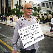 "An elderly man stands in front of Parliament building in Athens, Greece with a card around his shoulders reading ""I thank the young people that gave me the opportunity to be with them in this peaceful demonstration"". Image © Angelos Giotopoulos/Falcon Photo Agency"