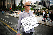 """An elderly man stands in front of Parliament building in Athens, Greece with a card around his shoulders reading """"I thank the young people that gave me the opportunity to be with them in this peaceful demonstration"""". Image © Angelos Giotopoulos/Falcon Photo Agency"""